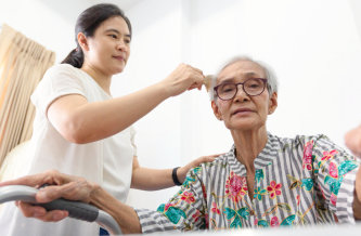 a caregiver combing the hair of a senior woman