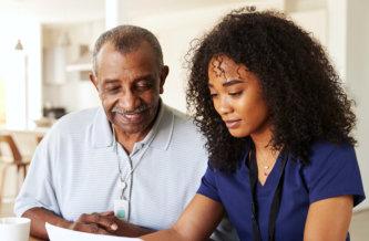 a caregiver and a senior man reading
