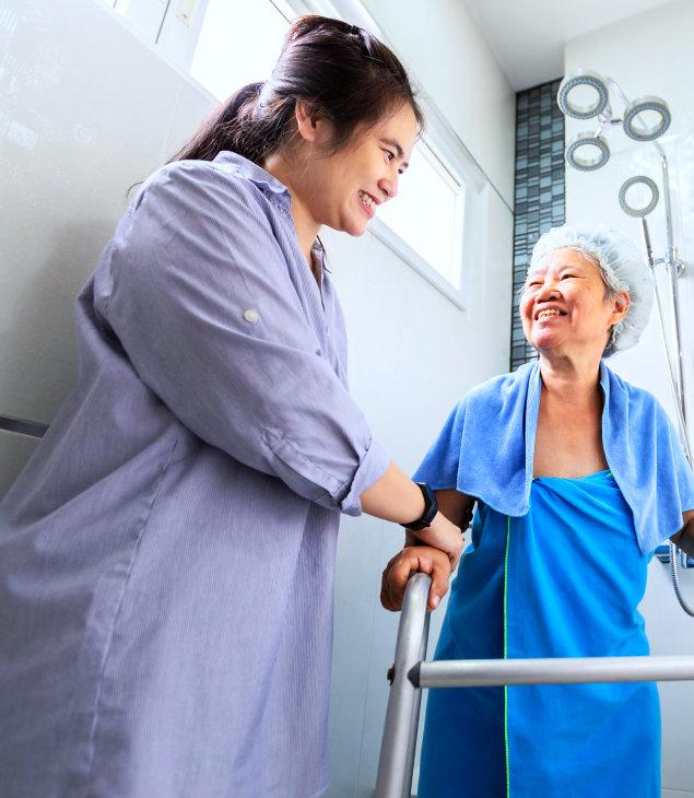 a caregiver assisting a senior woman take a shower