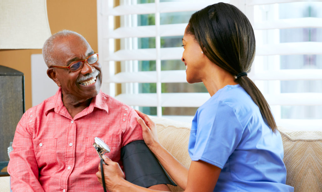 a caregiver checking the blood pressure of the senior man