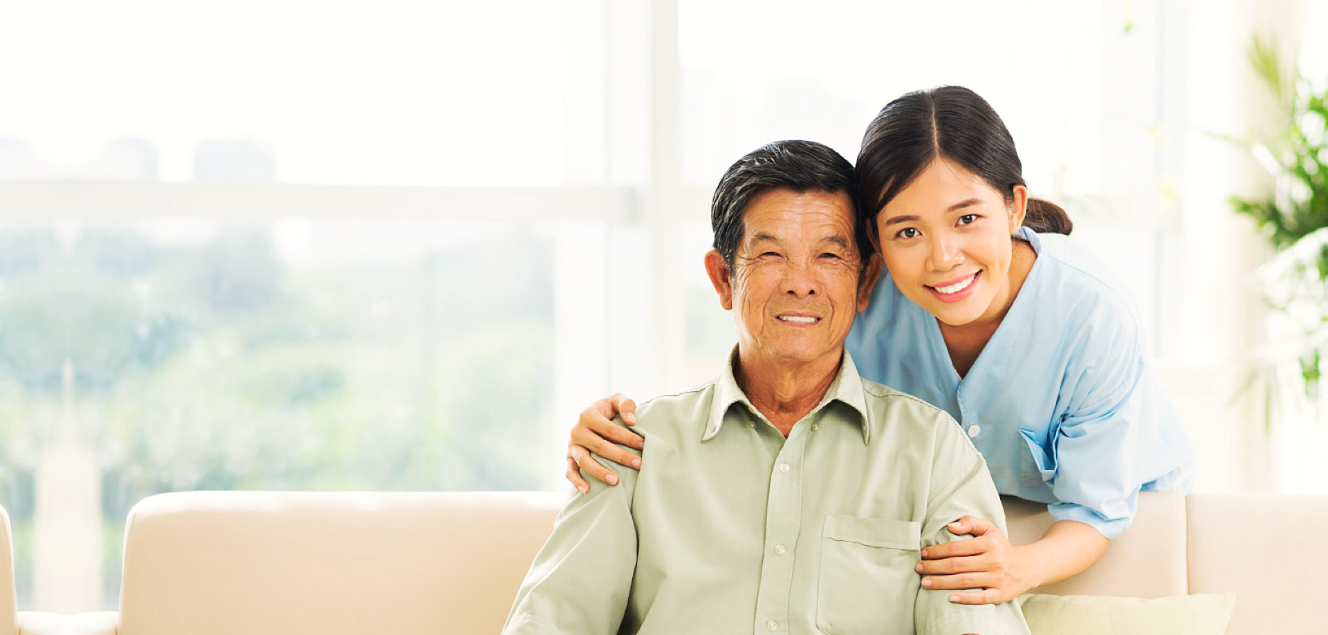 a caregiver and a senior man sitting on a sofa smiling