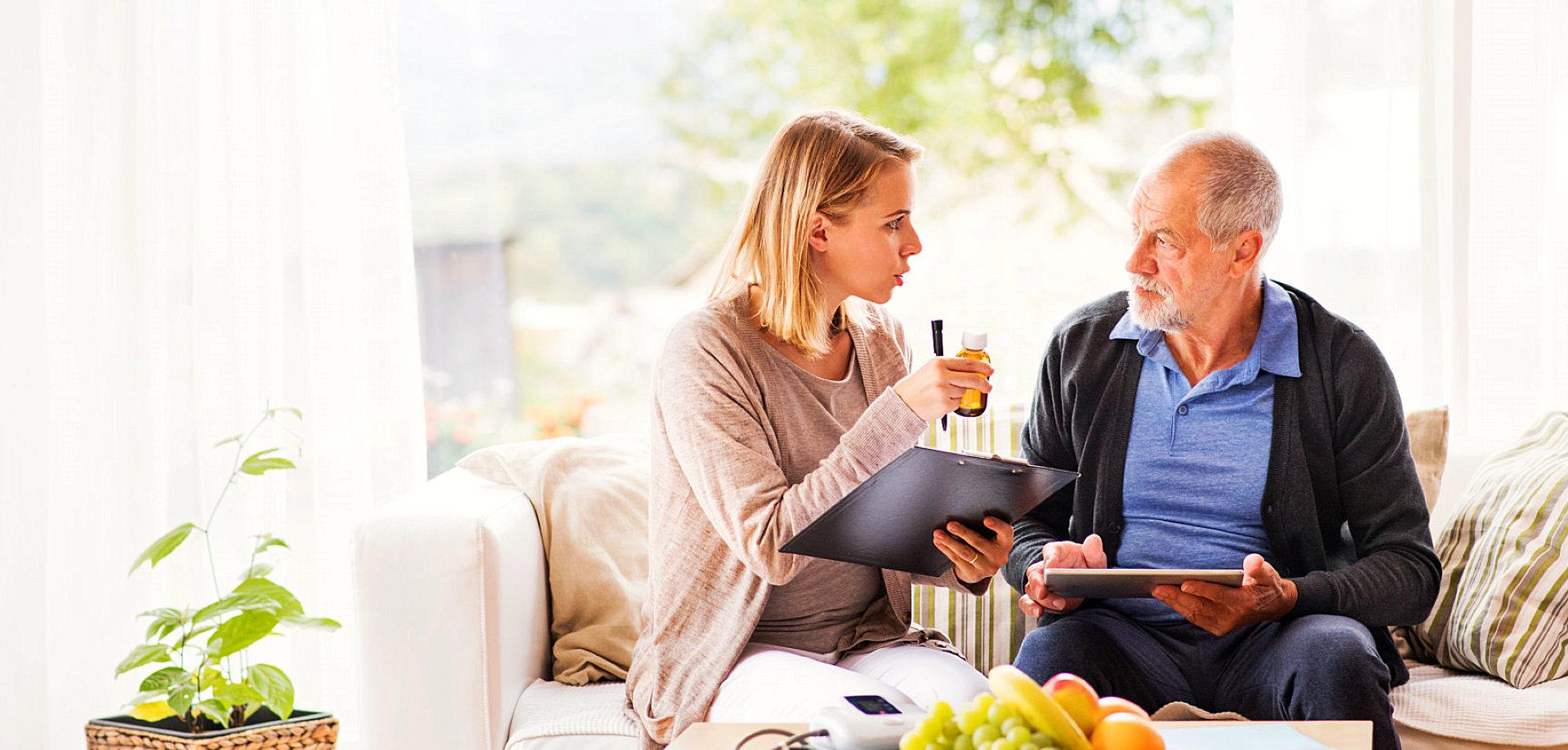 a caregiver giving medicine to a senior man