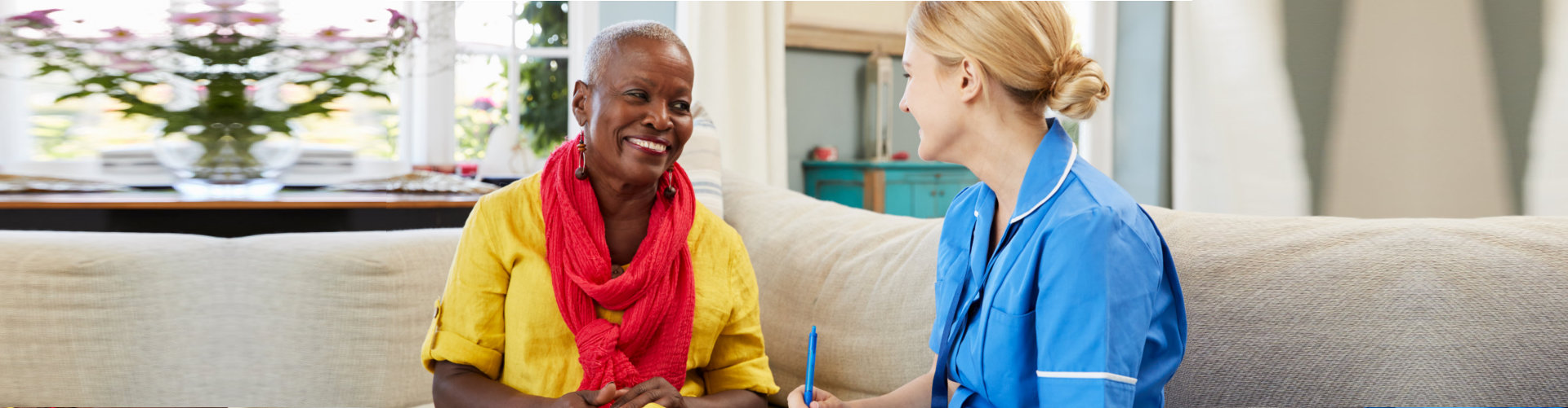 happy senior woman and caregiver talking
